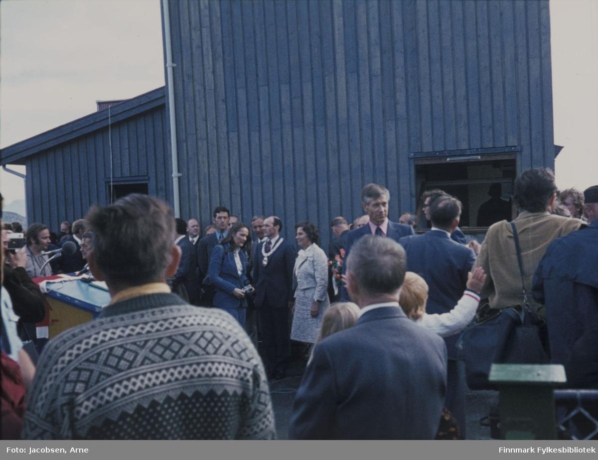 Samferdselsminister Annemarie Lorentzen med daværende ordfører Arnulf Olsen foran tårnet på Hammerfest Lufthavn under åpningen 30. juli 1974. Talerstolen står til venstre på bildet og i forkant til høyre ses et gjerde. Bak damen i blått, mulig en journalist, står Erling Jensen som var ordfører før Arnulf Olsen. Mye folk møtt fram til den store begivenheten.