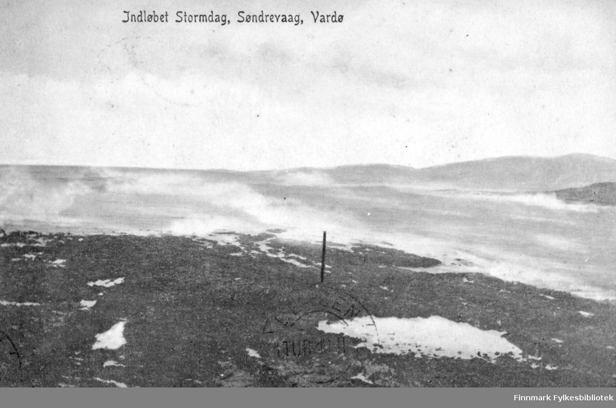Postkort fra Vardø. På fotografiet ser man innløpet til søndrevåg i Vardø en stormdag. Havet går hvitt og bølgene slår opp mot fjæra. Midt på bilde står det en stolpe