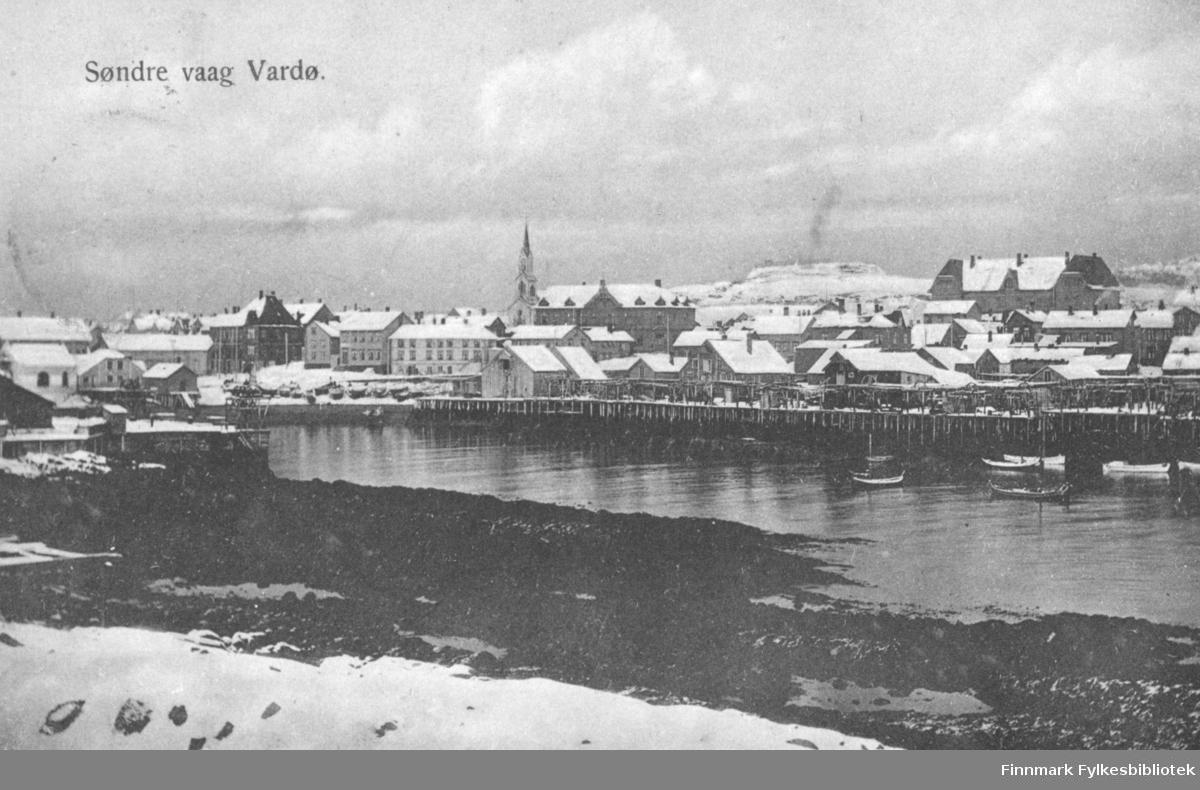 Postkort fra Vardø. På fotografiet ser man et parti av Søndre vaag i Vardø. Sjøen er rolig med noen båter på. Langs havna ligger det flere pakkhus. Det er snø øverst i fjæra. Midt blandt bygningene på bildet ser vi kirken. Til høyre ligger den gamle barneskolen. Det ligger snø på takene og på bakken