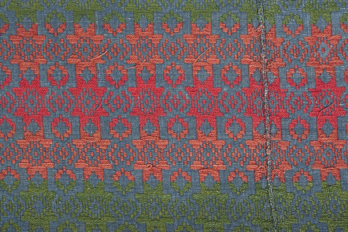 """Täcke vävt i opphämta. Blå bottenfärg, tvärgående ränder i grönt och två nyanser rött. De röda partierna är olika breda, de gröna är samtliga smala, förutom längst ut i kortsidorna. Ytmönster av stjärnor och staplade geometriska former. Stjärnor i den blå bottenfärgen, mellanrumsformer i rött respektive grönt. Bård längs långsidorna i avvikande mönster. Ytterst längs långsidans kanter en 10 mm kort, ej uppklippt frans av ullgarnsinslaget. Smal fåll i kortsidorna. Täcket är ihopsytt på mitten av två delar. Broderad märkning: """"SPD 1819"""" i rosa korsstygn, intill ena långsidan mitt på täcket, på en omönstrad ruta av bottenväven.Varp i indigoblått 1-trådigt z-spunnet lingarn, ca 15 trådar/cm.Botteninslag samma som varpgarnet, 11 inslag/cm.Mönsterinslag i grönt och i två nyanser rött 2-trådigt s-tvinnat ullgarn, ca 10 inslag/cm.Märkt på baksidan med påsydd tyglapp med texten: """"A. N° 105 Landstinget."""" Intill sitter en utställningslapp med texten: """"Hemslöjden""""."""