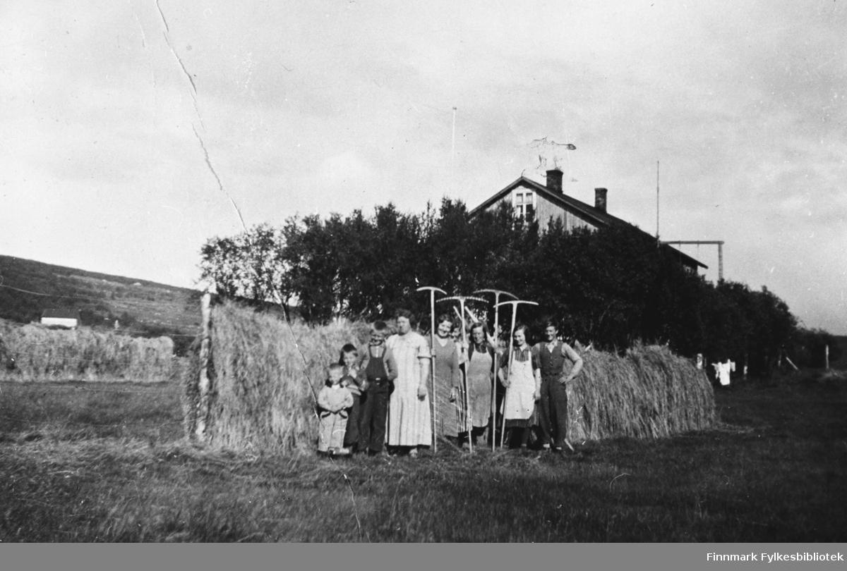 Slåttonn på Årnes, ca. 1936-1938. Fra venstre: Rolf, Bjarne, Nils, Esther, Gjertrud, Asbjørg?, to ukjente kvinner, Einar, alle med etternavn Betten. B 5540