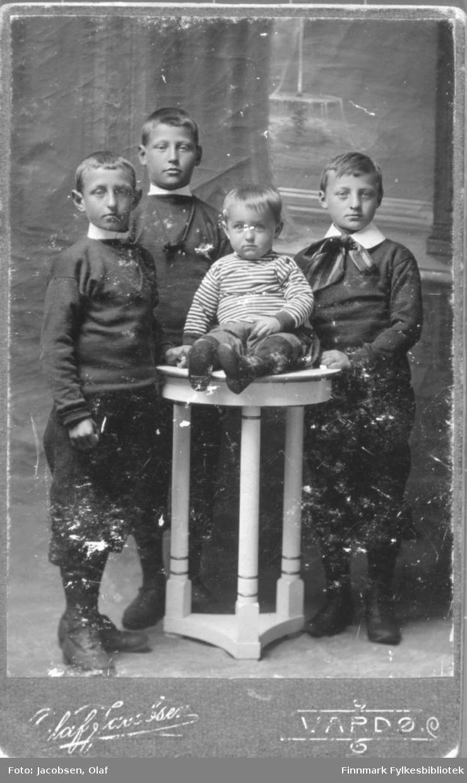 Portrett av fire 4 barn gutter bord ateliere studio knickers den ene gutten har sløyfe i halsen, hvit skjorte malt bakgrunn tepper  Albumet med bildet kommer fra Ekkerøy, kanskje de kommer derfra.