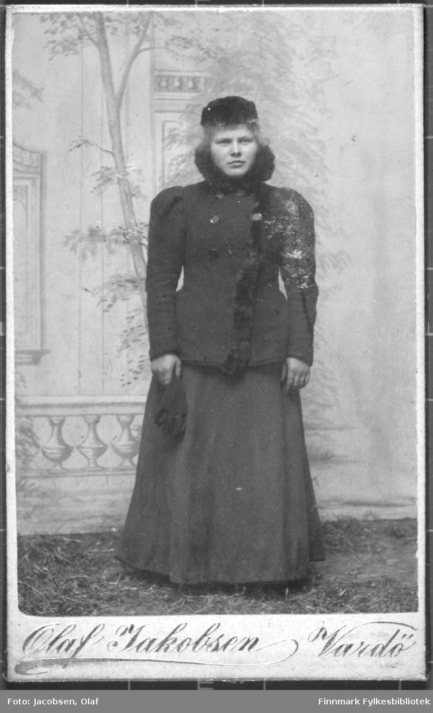 Portrett av ei kvinne i skjørt kjole og jakke med lange ermer holder hansker i hånden lue hatt på hodet malt bakgrunn ateliere studio.  Albumet med bildet kommer fra Ekkerøy, kanskje hun kommer derfra.