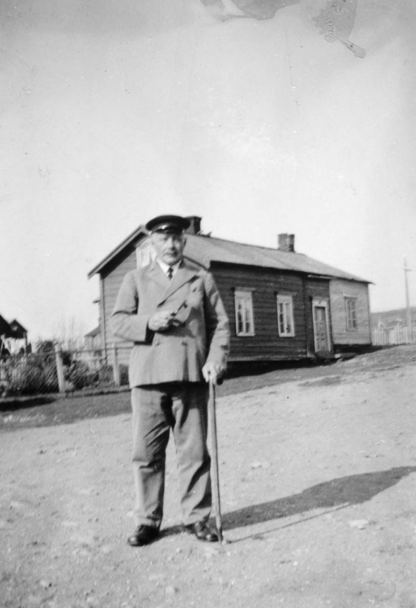 Påskrift på bildet: 'Lærer Alfred Korby utfor Kaisas hjem (Pedersens gamle smidje)'. På bildet kan man se Alfred Korbi som står med en stokk i hånden foran et lite trehus. Han er kledd i dress: jakke, bukse, sko og hatt. På huset i bakgrunnen kan man se tak, vindu, dør og skorstein. Bildet trolig tatt på 1930-tallet (kanskje 1933).