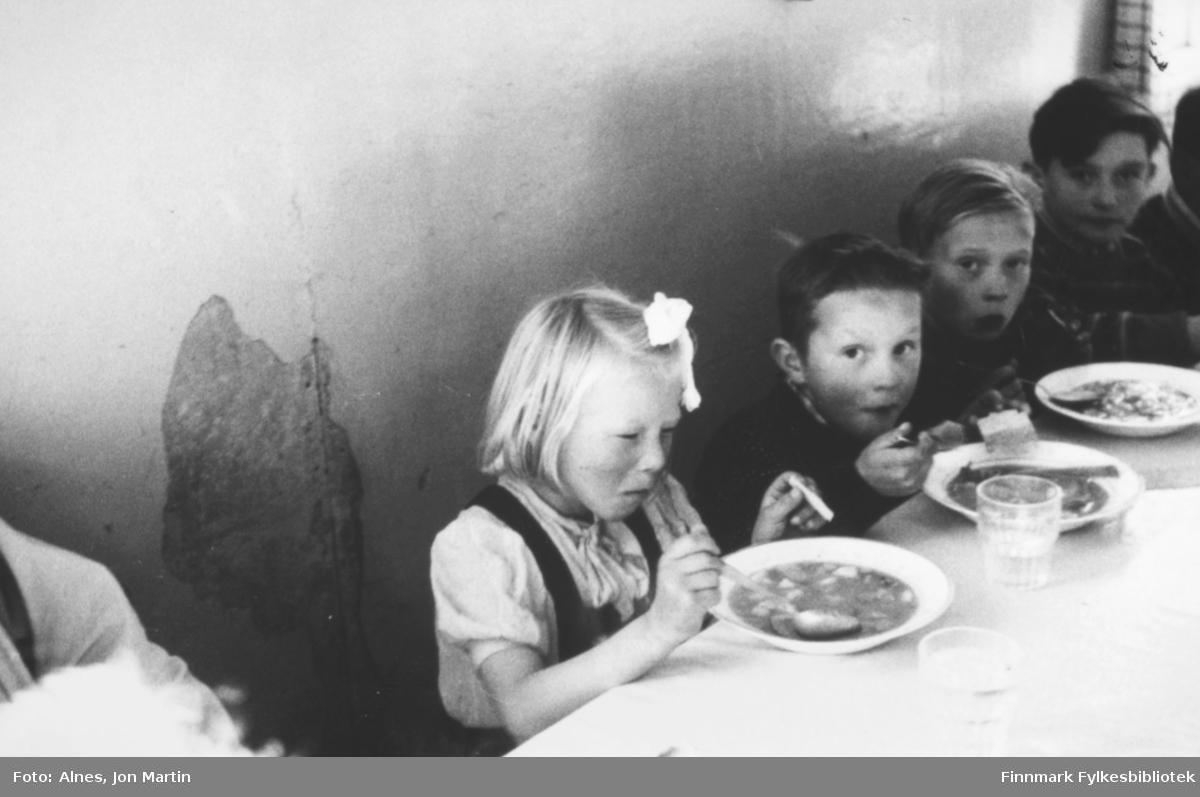 Elever som bodde på skoleinternatet i Øksfjord ved middagsbordet, 1953. Internatet var i den gamle skolebrakka i fiskeværet. Det ser ikke ut til at jenta nærmest kamera likte maten!