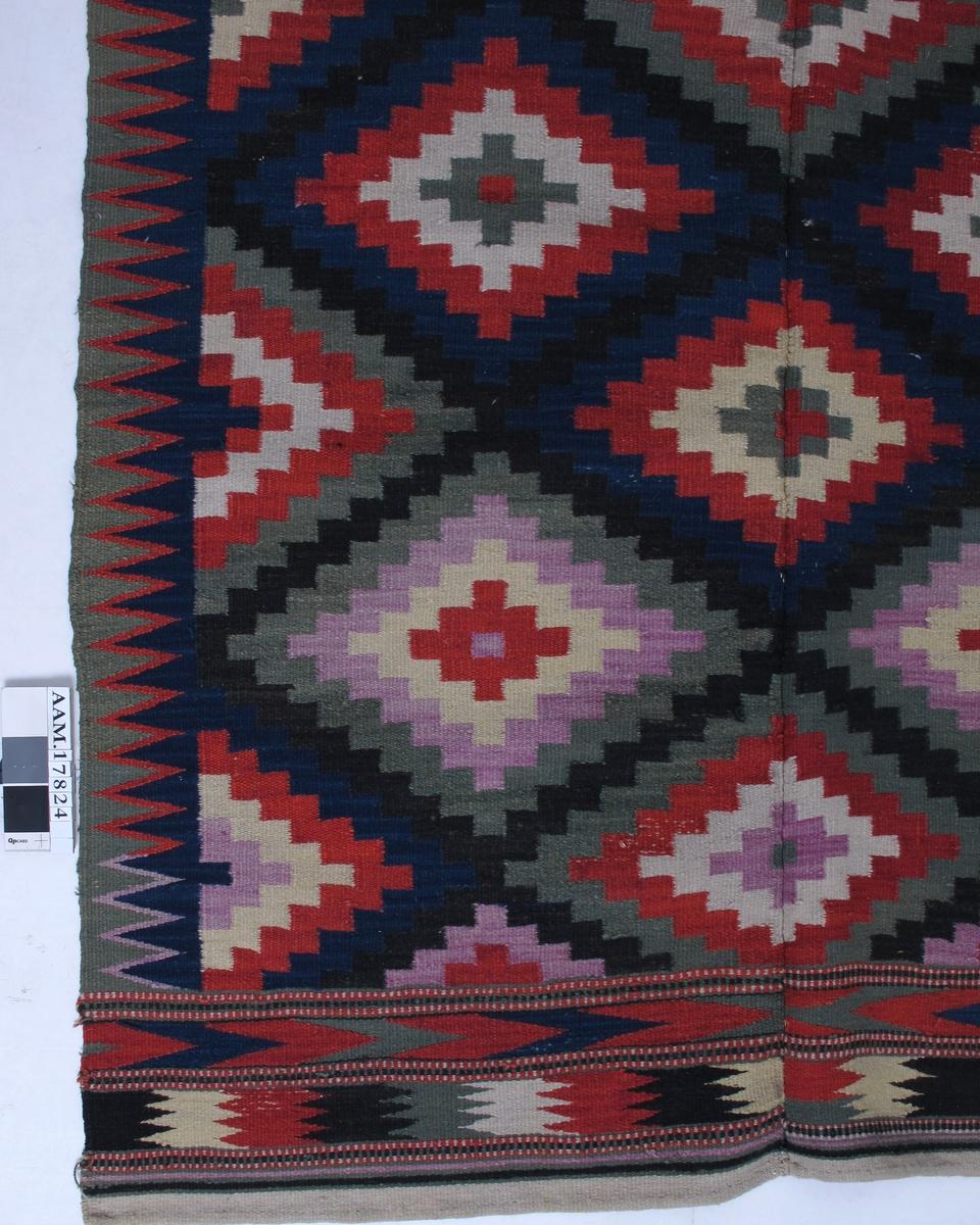 Åkle, med lin renning, ull islett.  Hjemmespunnet og hjemmevevd.  Diagonalrutet med svart.  Rombemønster i dypblått, dyprødt, grågrønt, blekgult og svakt lilla.  Avsluttes oppe og nede med to lynildborder i samme farger.  Se AAM.17824. Tilstand:  Meget god.