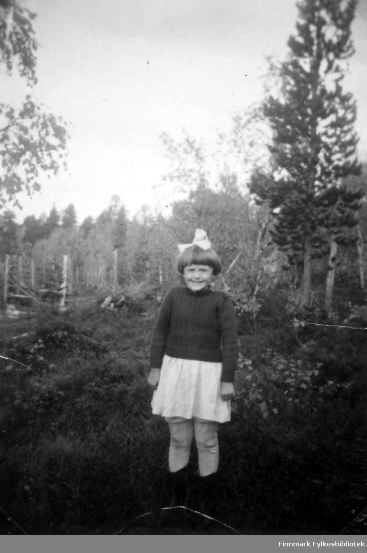 Fotografi av Edith Stenbakk søster til Agnes Randa. Bildet er tatt i bygda Namdalen i Pasvik. I bakgrunnen ser vi mange trær. Edith er kledt i en mørk genser og et hvitt skjørt. I håret har hun en hvit hårsløyfe