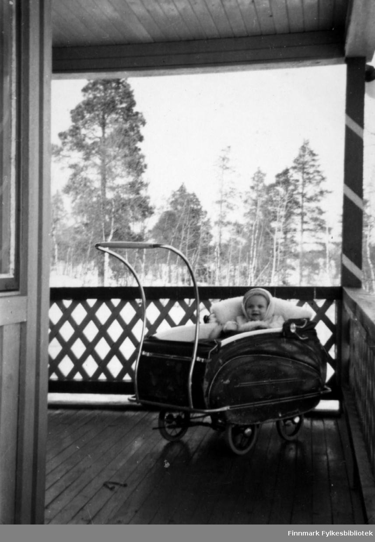 Fotografi av Vivi Stenbakk som sitter i en skinnpose oppi ei barnevogn. Hun har en hvit lue på seg. Vogna står ute på en veranda med overbygg og rekkverk. Det er høye trær framfor verandaen
