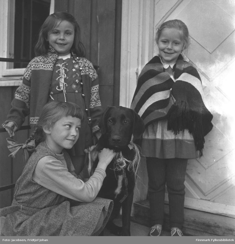 Tre små jenter og en hund fotografert på trappa til et hus. Jentene og nøyaktig sted er ukjent.