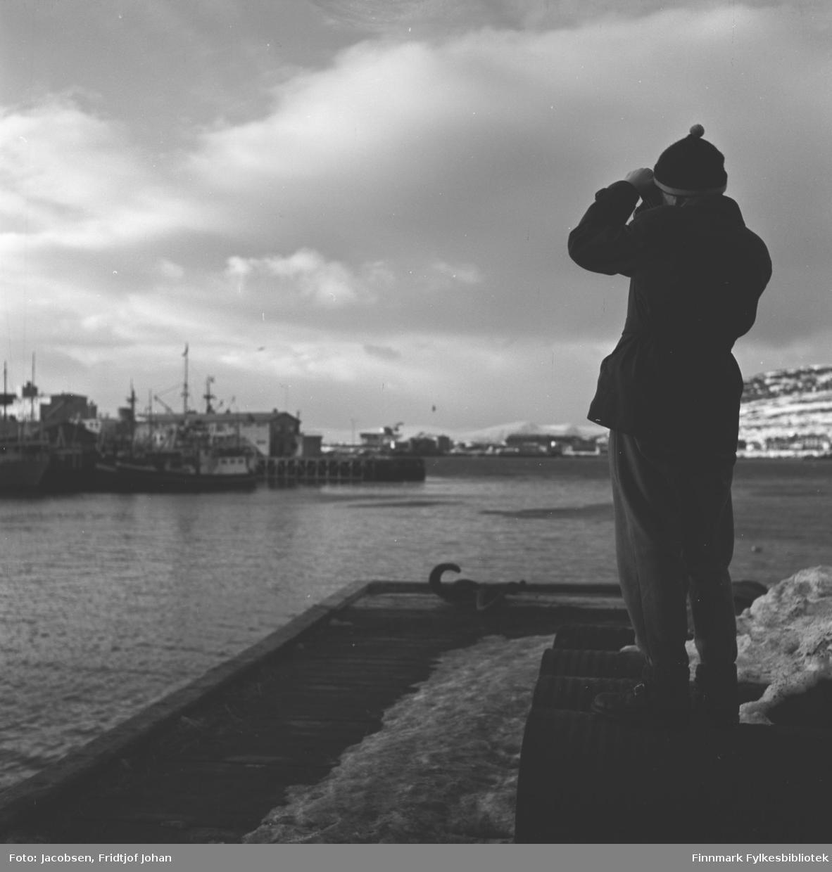 Arne Jacobsen står på Bangkaia og ser mot sentrumsbebyggelsen på andre siden av havna. Noe diffust ses bydelen Fuglenes i bakgrunnen.