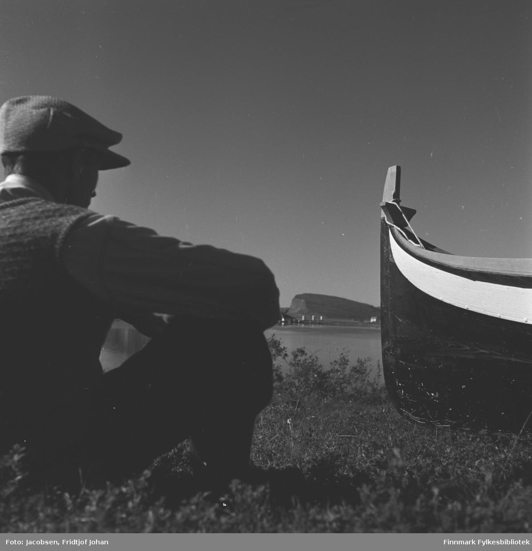 Arne Nakken ved siden av sin selvbygde Nordlandsbåt hjemme i Rypefjord. Shells tankanlegg på Rypklubbeidet og øya Håja ses mellom han og båten.
