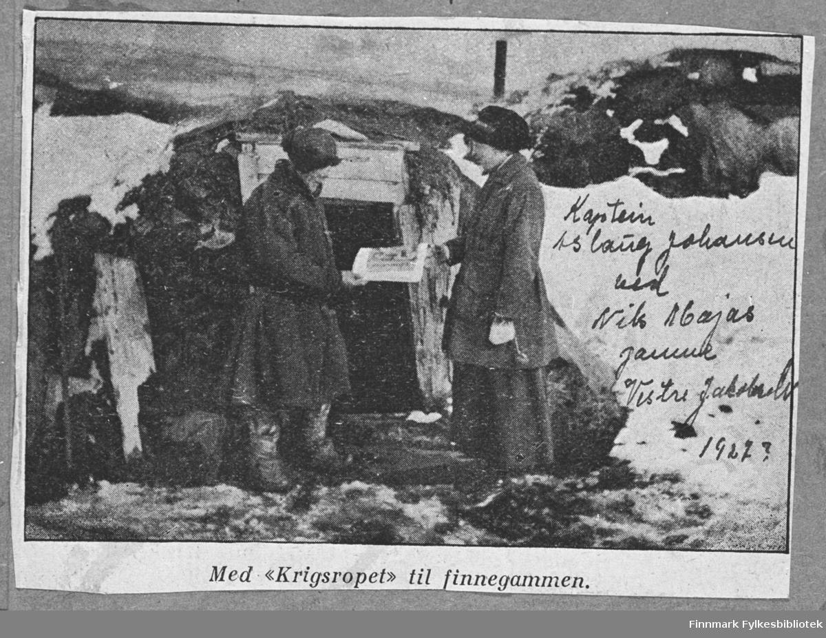 Nils Maja får 'Krigsropet' av Frelsesarmeens kaptein Aslaug Johansen. Maja-Nils står foran gammen sin og tar mot avisen. Det er snø på marken. Bildet er repro fra et avisklipp og kvaliteten er meget dårlig.