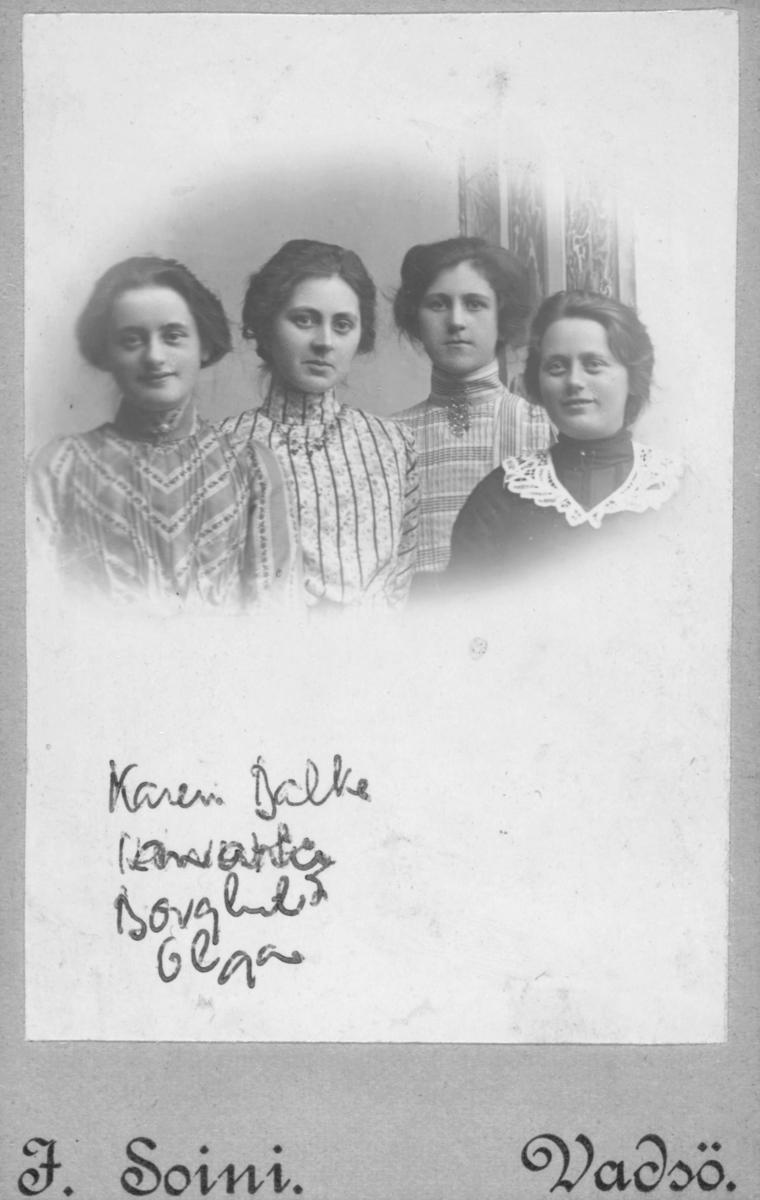 Gruppebilde av  fire unge kvinner, fra venstre: Karen Balke 16 år,  Henriette Steen 23 år, Borghild Steen 16 år og Olga Marie Pedersen 17 år, fotografert Sommeren 1903. Venninnene er kledt i vakre bluser med smykker eller nål i halsen. Henriette og Borhild Steen er døtre av Toldinspektør, Kst.Havnefoged, Lodsoldersmand og Indrulleringsbetjent Marius Emil Steen som var født i Bergen i 1850 og gift med Theodora Olava Steen, bosatt i Vadsø på denne tiden.  Bildet er tatt hos fotograf Jasper Ulrik Soini i Vadsø. Jasper Soini var født 20.september i 1872 i Hammerfest og døde 2.september 1905 i Vadsø. Han virket i Vadsø tidlig på 1900-tallet. Han hadde samme atelieradresse som Emilie Henriksen, som kanskje tok over forretningen etter Soini. Soine var sønn av skomaker Isak Isaksen Soini og kona Marie Christine som kom fra Øvre-Torneå i den russiske delen av Finland. i 1875 bodde familien på adresse Kirkepladsen 56a, ti år senere hadde de flyttet til Raadhusgade 67 i Hammerfest. Soini flyttet til Vadsø hvor han fikk en sønn i 1904, Leofred, som døde i 1907. Barnets mor giftet seg med en annen før barnet ble født og flyttet til Vardø. Soini døde av tuberkulose i 1905 og var ugift.