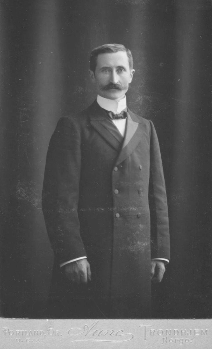 Portrett fra en ukjent mann med bart og dobbeltspent frakk, stiv skjortekrage og tversoversløyfe. Fotografert hos fotograf Aune i Trondheim.