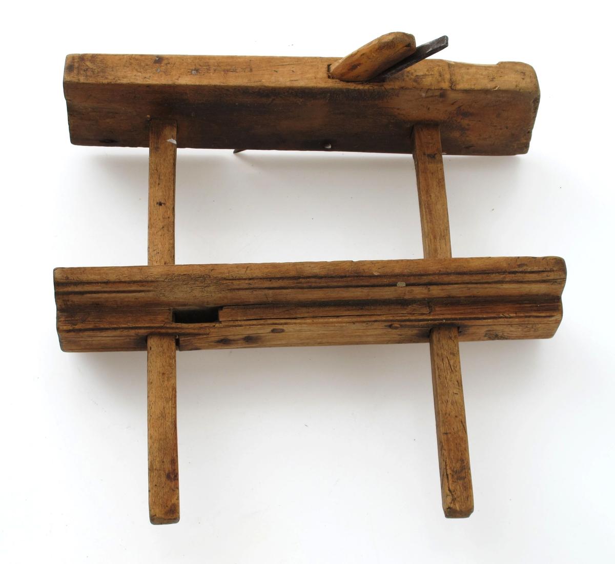Høvel,  av løvtre , jern.   Nothøvel med langsgående blad og smalt tverrstilt  blad pm. To firkantede sidestenger. Tilstand: rusten, avskavet i sålen.