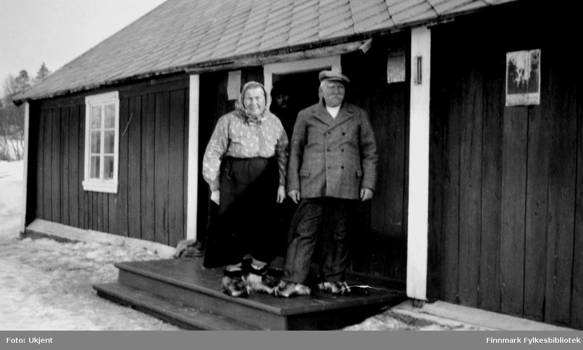 Gargia fjellstue 1934. Bildet er tatt i forbindlse med besøket av  kronprins Olav og kronprinsesse Märtha  under deres påsketur over Finnmarksvidda. Bildet viser oppsitterparet/bestyrerparet/ekteparet Else Lovise og Magnus Pedersen som står på trappen utenfor ytterdøren på Gargia fjellstue. Begge har samiske skaller på bena. Else Lovise er kledd i skjørt og bluse med skaut på hodet. Magnus har på seg dobbeltspent dress og skyggelue.
