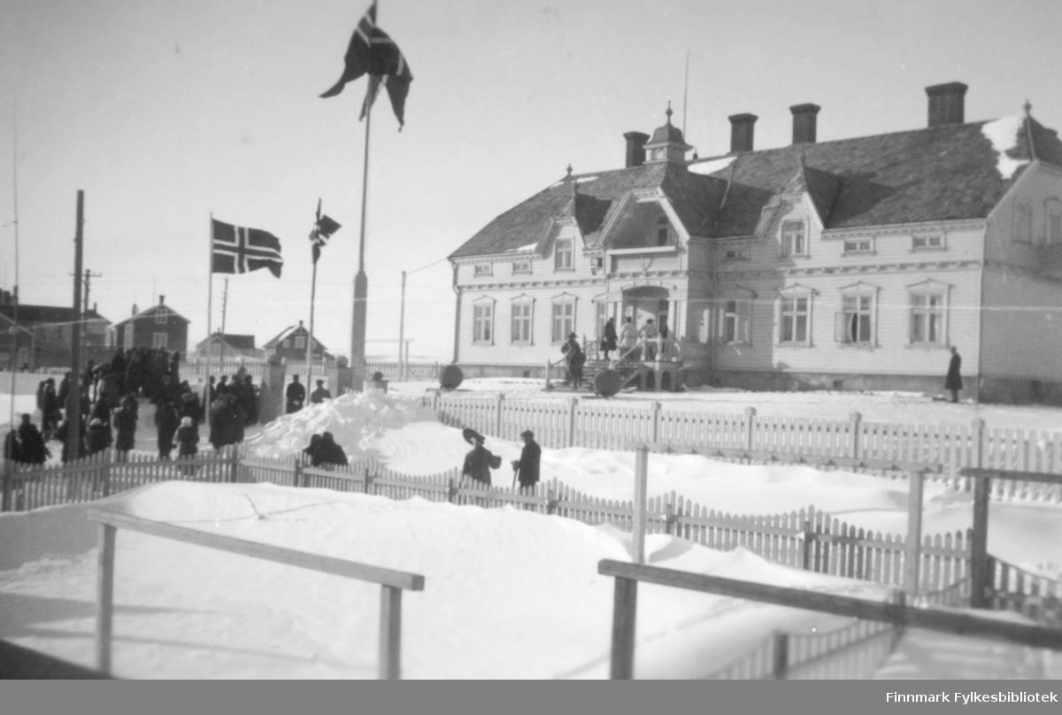 Kronprinsparet Olav og Märtha avsluttet sin påksetur gjennom Finnmarksvidda i 1934 i Vadsø. Bildet viser Fylkesgården før skolebarna og speiderne defilerte foran hovedtrappa og hilste gjestene. Fotograf: ukjent.