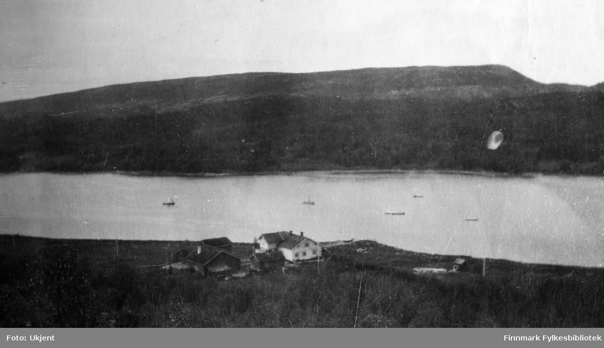 Gården Strømsnes i Jarfjord, bildet tatt fra høyden ovenfor gården sommeren 1923. Man kan se at gården ligger ved havet og enkelte båter ligger ikke langt unna. På huset kan man se vindu og skorstein. Huset er omringet av gjerder.