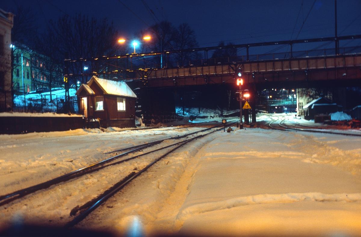 """Vinterkveld på Loenga stasjon, stillverk III. Utkjørhovedsignal N og høyt skiftesignal Zn samt hovedlinjesignal. Signalet som vises er """"Kjør fra togvei med avvikelse over en eller flere sporveksler"""", """"Hovedbanen"""" og """"Skifting forbudt. Loenga var forgreningsstasjon mellom godstogsporet på Hovedbanen og Gjøvikbanen ved Kværner. Denne delen av stasjonsområdet hadde håndstilte sporveksler, og det var sporskifteren i """"Stillverk III"""" som la togveier. Hovedsignalet var felles for alle togspor. Bak hovedsignalet sees Oslo bru, i 1989 omdøpt til Geitabru, der Oslogate går over. Gamlebyen."""
