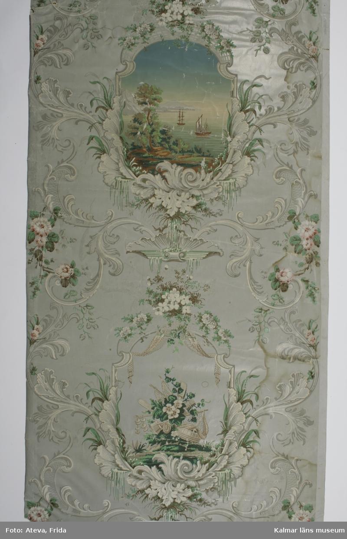 KLM 10626. Tapet. Tittskåpstapet. Av papper. 4 st tapetbitar. Tryckt tittskåpstapet med grå satinerad botten. Scenerna har landskap med båtar, byggnader och natur. Inramade med blommor och blad. Mönster i nyrokoko i färgerna grått och schweinfurtergrönt. Scenernas bottnar är satinerade i blått, ljusrosa och grönt. Datering: 1840-1850-tal.
