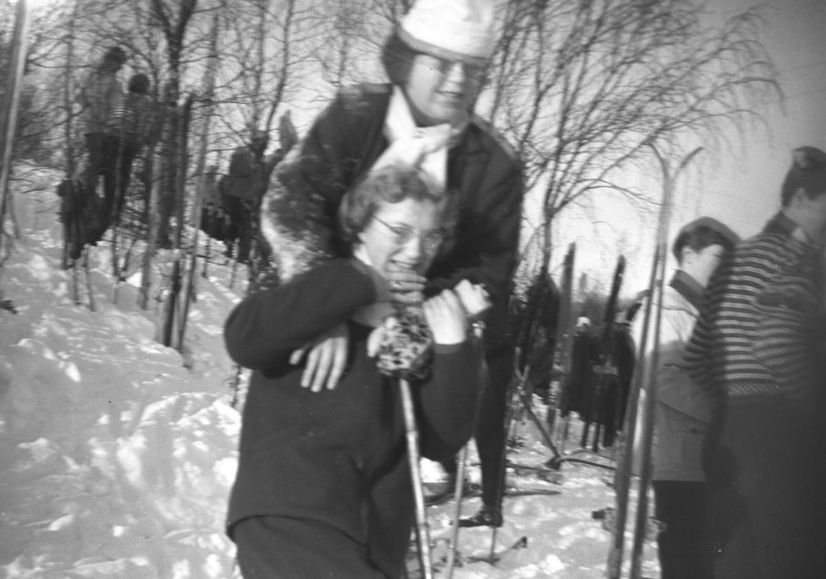 Mye folk er ute og koser seg i snøen. Nærmest står en dame som heter Herdis og rett bak henne står Digmar. Etternavnet på damene er ukjent. Stedet kan være i eller rundt Vadsø.