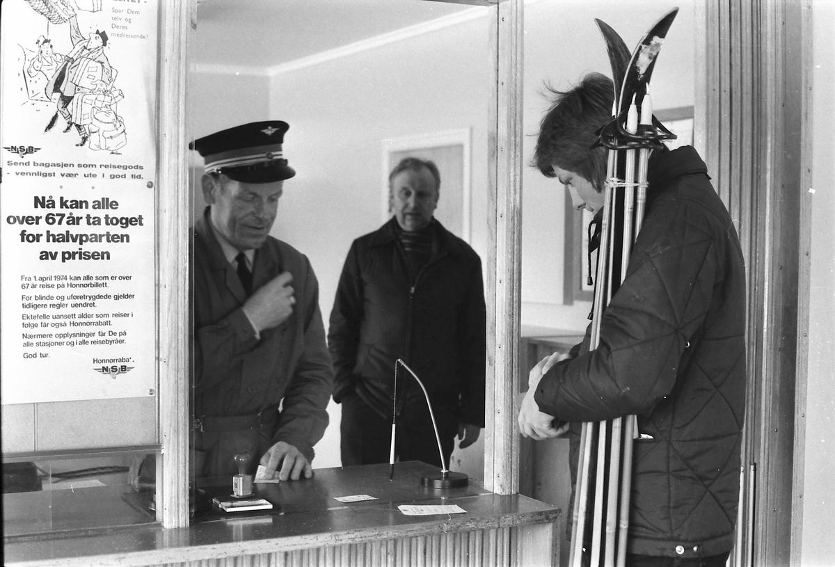Billettkjøp i billettluke Os jernbanestasjon, Os i Østerdalen. Pål Finn Moseng sender reisegods hos stasjonsmester Jon Kverneng. Magnus Borgersen i bakgrunnen.