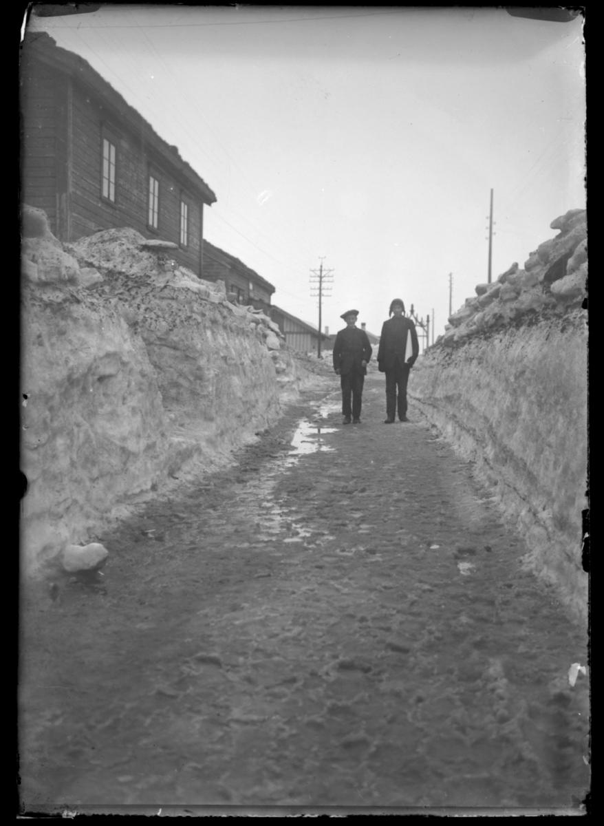 Vårløsning i Vardøs gater. To gutter står på en sølete og oppbløtt vei med høye, skitne skavler på sidene. I bakgrunnen festningsporten. Se også 93136-019
