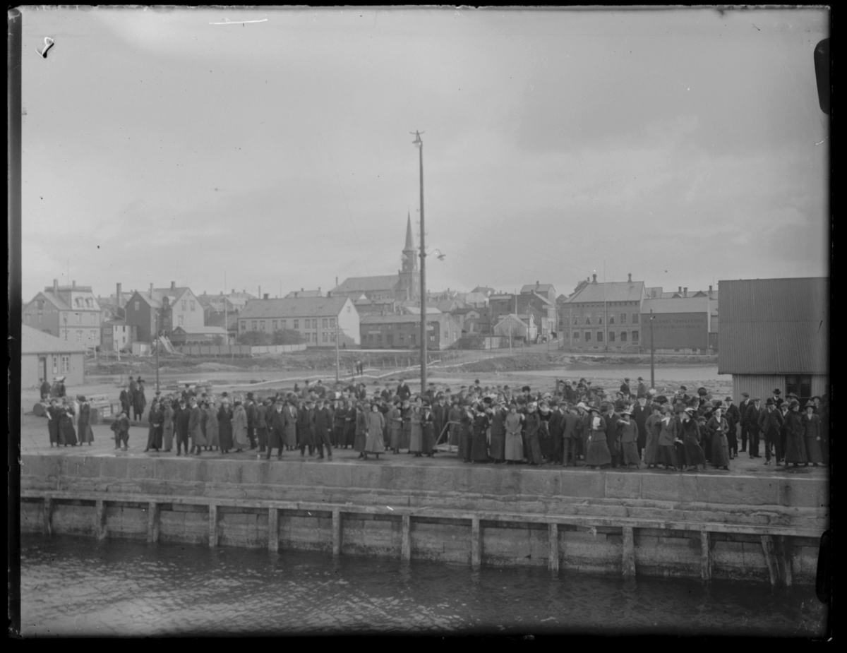 Kaia i Vardø fotografert fra båt, antakelig Hurtigruta. Det har samlet seg en folkemengde på dampskipskaia. I bakgrunnen ser vi byen med bl.a. kirka sentralt i bildet