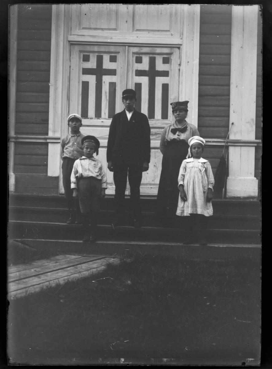 Boris Gleb. En mann, en kvinne og tre barn på kirketrappa, og vi ser den utsmykkete kirkedøra bak dem