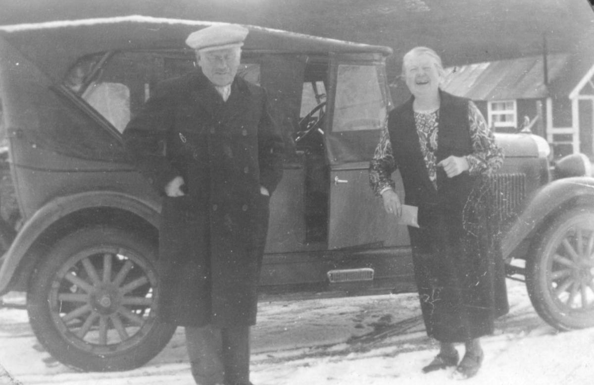 En mann og en dame står ved siden av en bil.