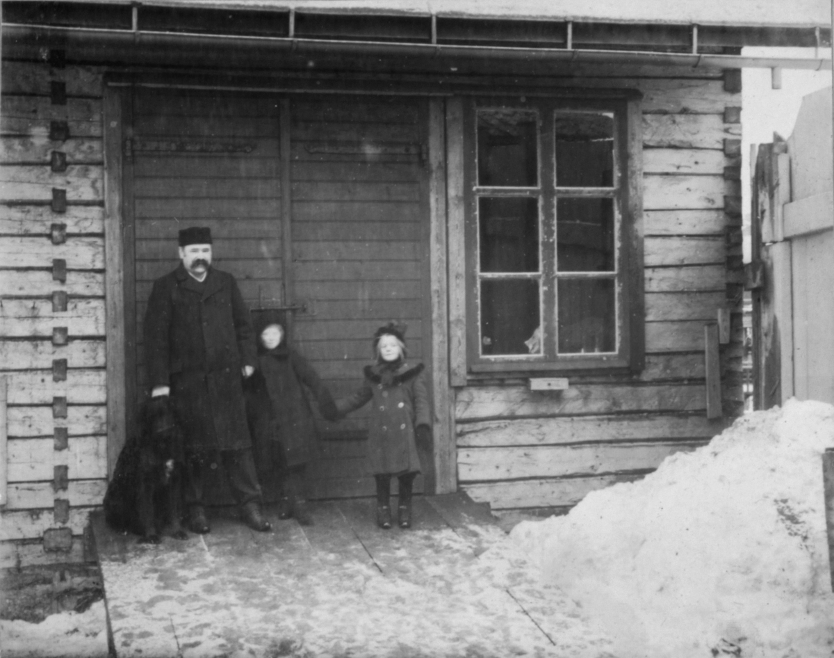 En mann og to barn står foran en port eller dør til en bygning. Til høyre for mannen en hund.Bygningen har et vindu til høyre. En stor snøhaug til høyre.
