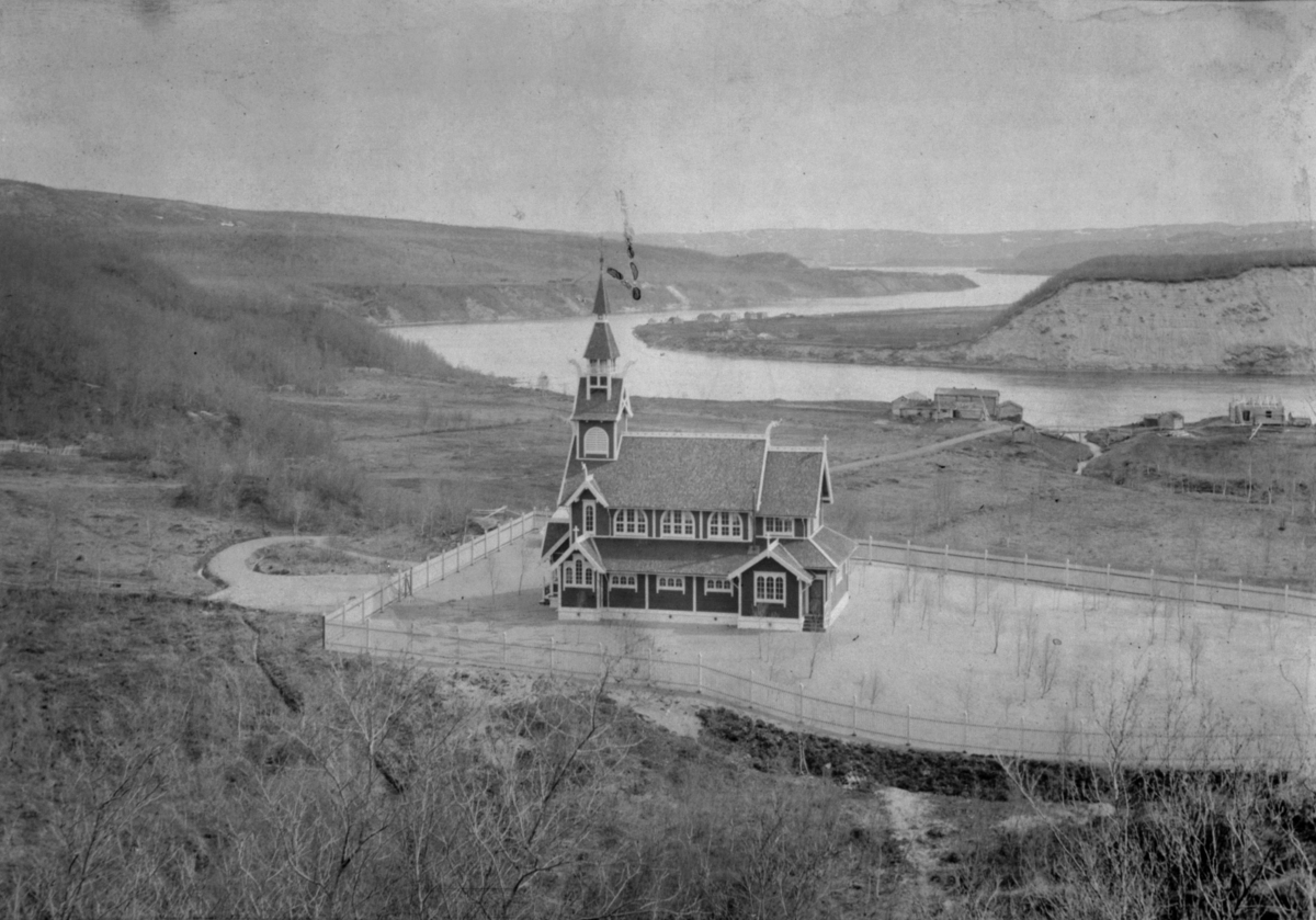Neiden kapell fotografen har stått på en høyde over kapellet. I bakgrunnen ser vi Neiden-elva og et par gårdsbruk.