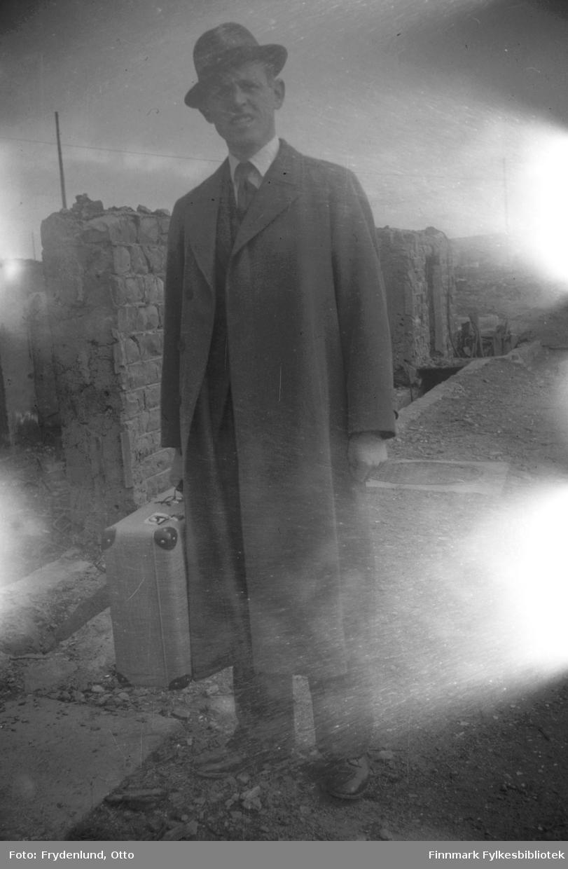 Politimester Egil Breen med koffert, hatt og frakk, ruiner i bakgrunnen