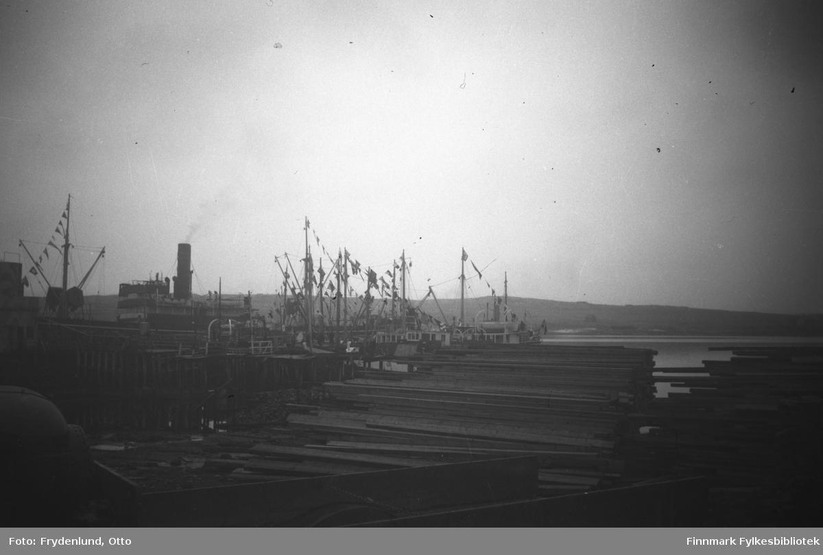Alle fartøyene på havna i Vadsø flagget i anledning Kong Haakons besøk i byen i 1946. I forgrunnen en stor plankestabel, materialer til gjenreisningsarbeidet
