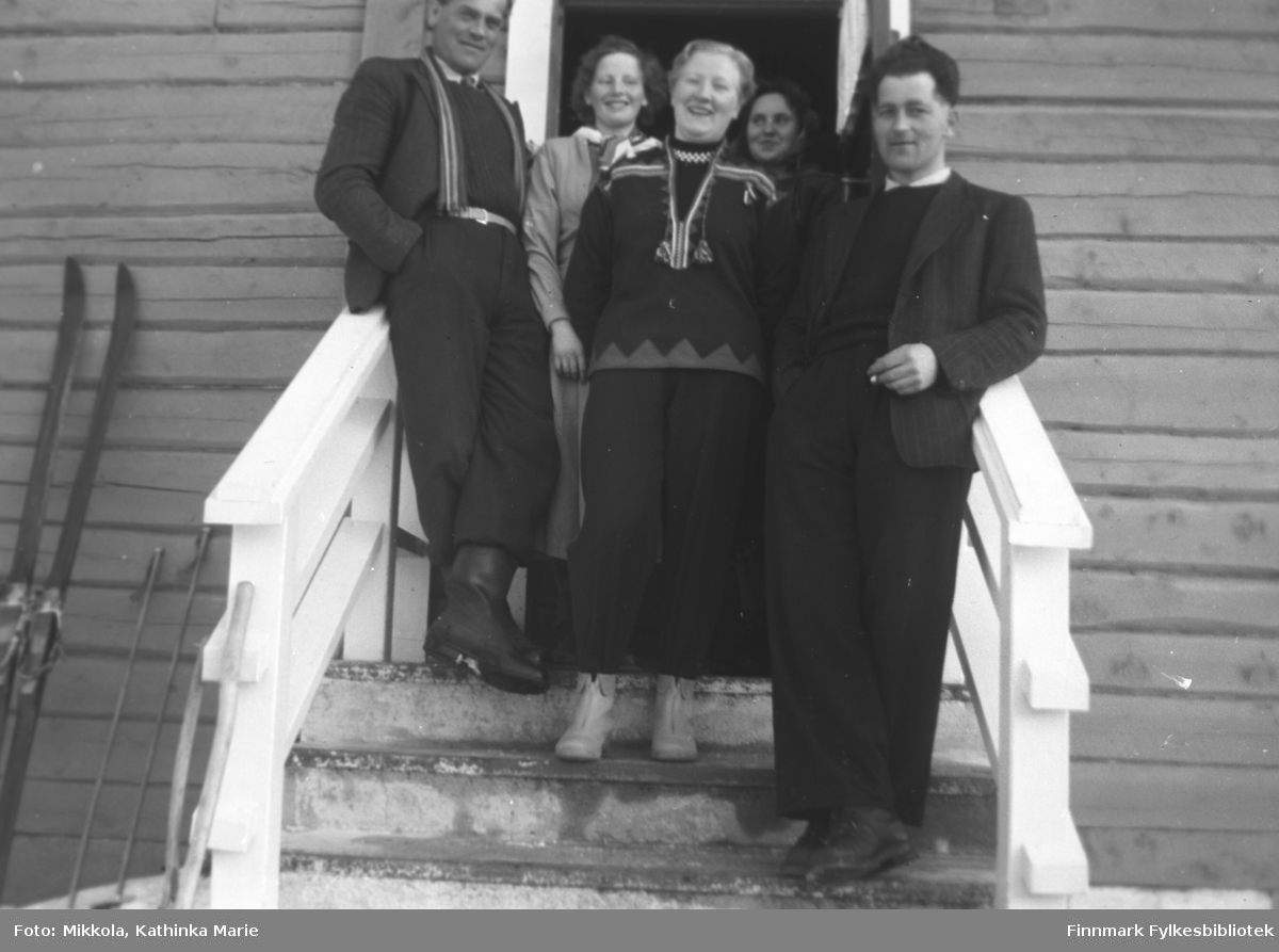 Gruppebilde på trapp, antakelig i Neiden. I midten, med samiskinspirert kofte - Herlaug Mikkola. Mannen helt til høyre: Odd Gabrielsen