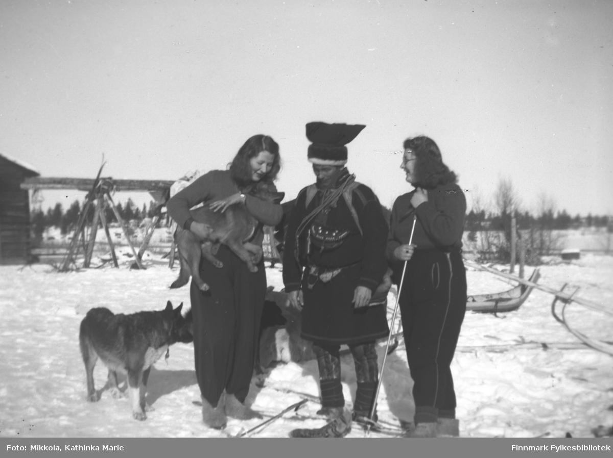 Den finske grensestasjonen Pakanajoki, 1937. Fra venstre: Kari Mikkola med hunden til skogvokter Antti Aikio, Ole Andreas Magga, Ingrid Mikkola. I bakgrunnen sleder og pulker, ei hytte og en vinterlagringsplass for høy