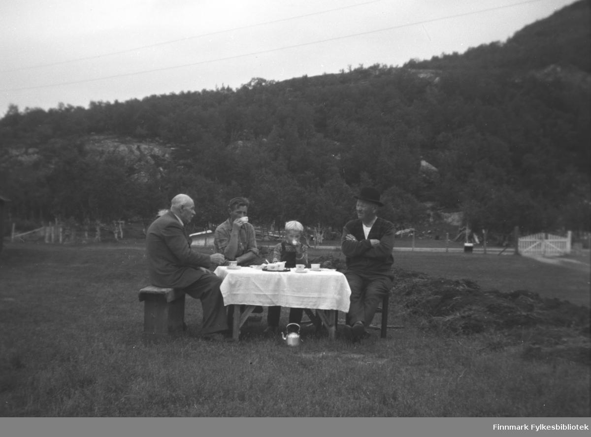 Kaffe utendørs på gården Mikkelsnes, ca. 1958-1962. Fra venstre: En ukjent besøkende herre, Halvor Lindseth, Sture Olsen Lie og Aksel Konrad Mikkola. Bordet er fint dekket med hvit duk