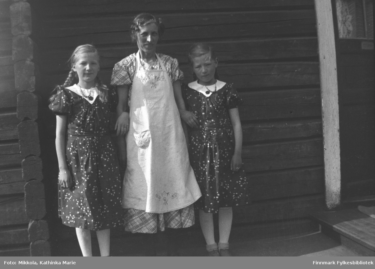 Valborg Nilsen arm i arm med jentene Gudrun (til venstre) og Kari Mikkola. Jentene har fine kjoler og kan være 9-12 år gamle. Bildet er tatt i Kirkenes