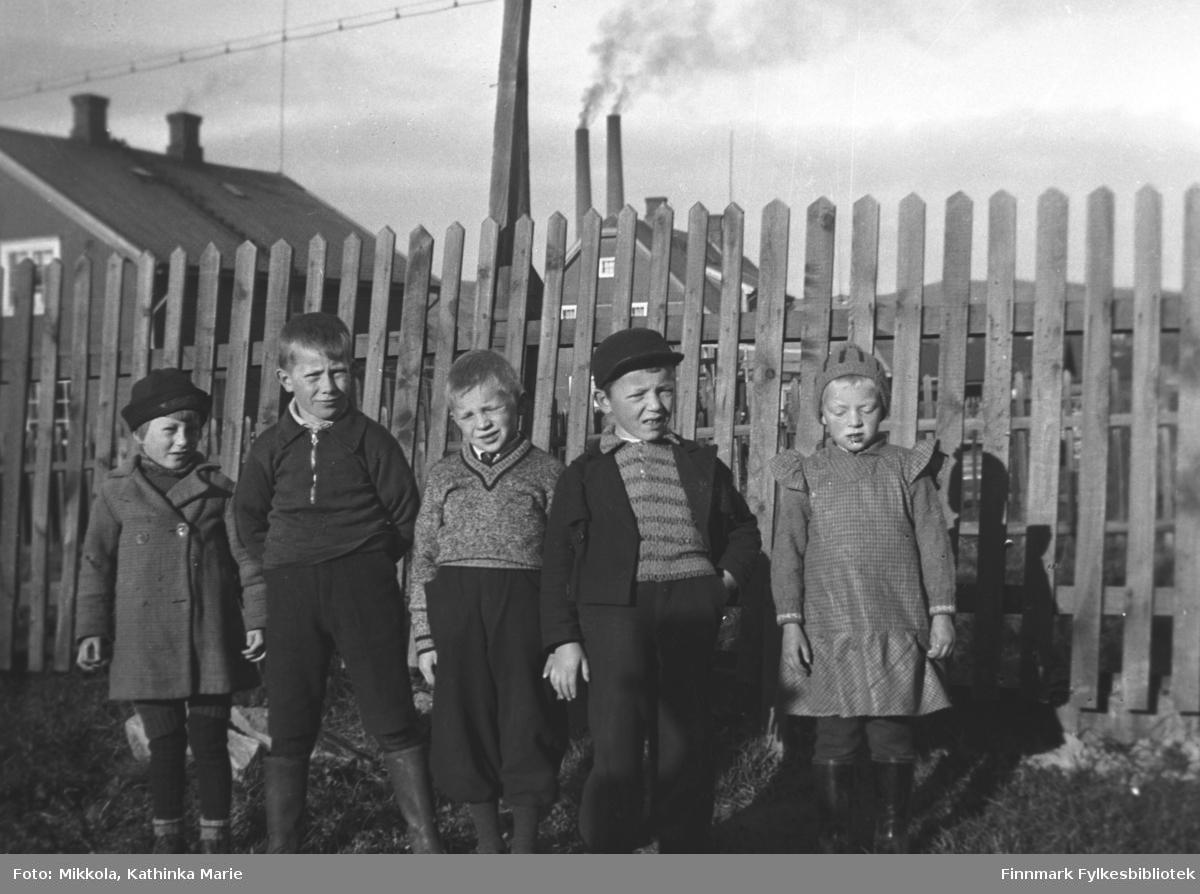 Barneflokk fotografert i Kirkenes. Til venstre søsknene Dagmar og Roald Larsen. I bakgrunnen ser vi to piper fra Sydvarangers dampsentral