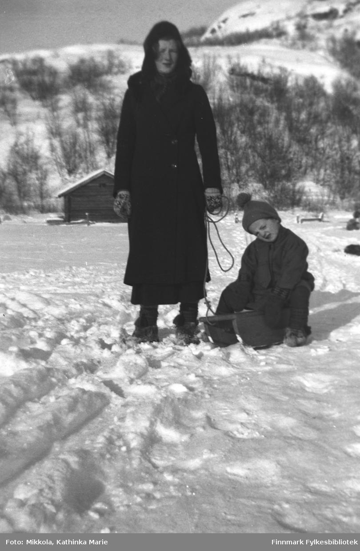 På kjelken Astrid Mikkola, søsteren Marine står i snøen ved siden av. Begge har skaller på bena, og Marine har fine selbuvotter
