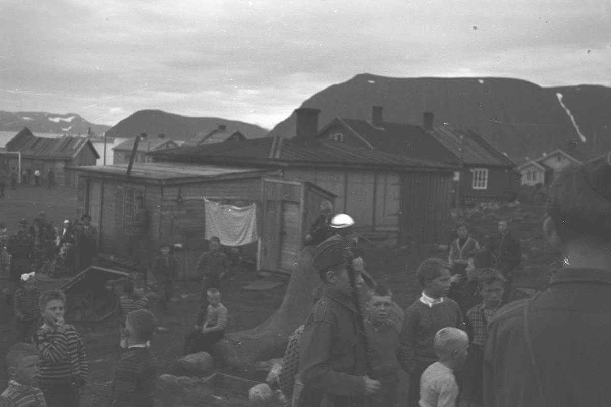 En gruppe barn er samlet på en slette foran noen hus og brakker. Sted og anledning er ukjent, men det kan være en korps- eller speidersamling.