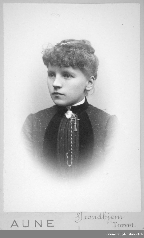 Portrett av en dame iført en mørk overdel. En liten flik av den hvite skjorta/blusen hun har under vises i halsen. Der ses også et langt kjede.