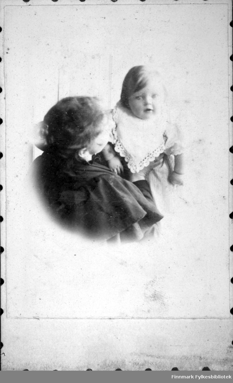 Portrett av en kvinne som holder et lite barn i armene sine. Damen har en mørk bluse og er fotografert med ryggen til. Det lille barnet har en lys, kortermet overdel med en smekk med blondekanter rundt halsen.