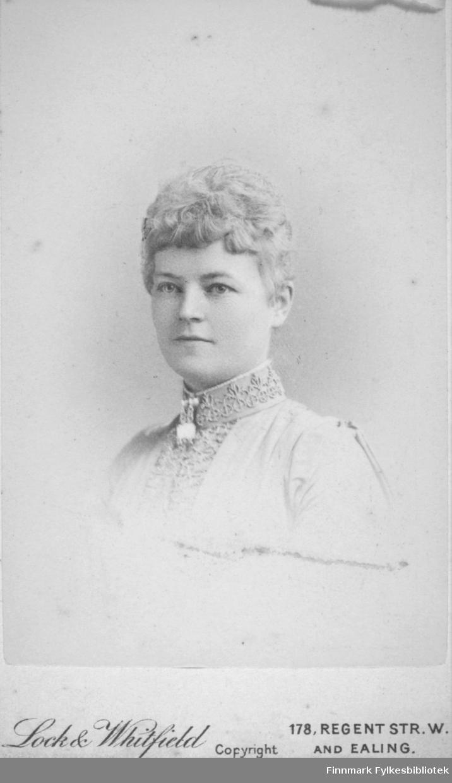 Portrett av en dame iført en lys bluse eller jakke. Den har høy krage med mønster og noe pynt er festet foran i halsen på den.