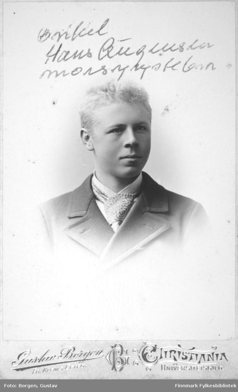 Portrett av Hans Augensen. Han har en mørk dressjakke, hvit skjorte og et mønstret slips på seg.