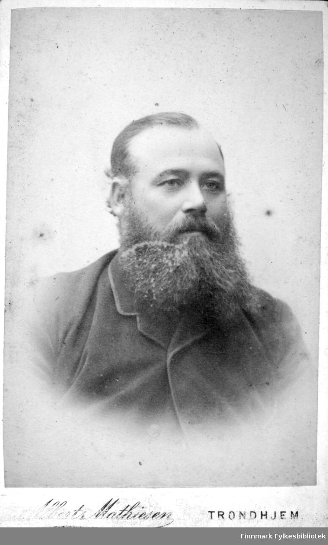 Portrett av en mann med helskjegg. Han er iført en mørk dressjakke.