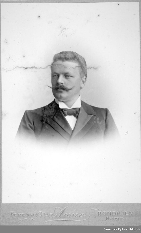 Portrett av en mann med mørk dressjakke, hvit skjorte med høy krage og sløyfe i halsen.