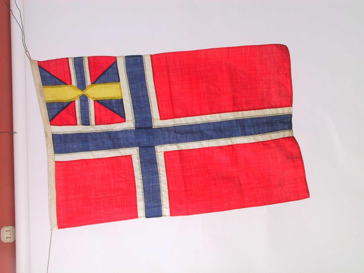 Unionsflagg av ull. Lite flagg med lerretsbånd med snor.  Endel reparert i sømmene, noen få, små møllhull.