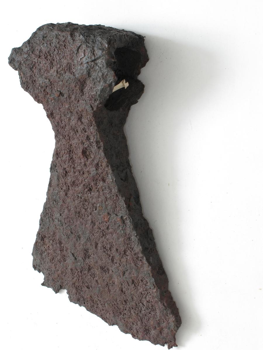 Øks av jern, nærmest som Jan Petersen: Vikingesverd,fig. 43 - L-typen - men med sterkere svunget overkant og kortere underkant. Forrustet. 3 av skaftflikene mangelfullt bevart.