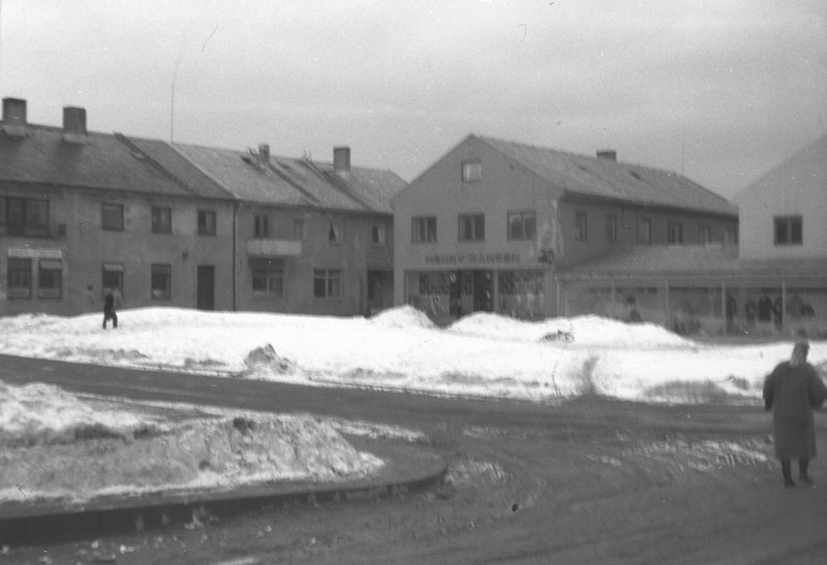 Vinterbilde av torget i Vadsø. Noen få personer er ute og går.